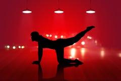 女子瑜伽在木地板红色背景的剪影锻炼 免版税库存照片
