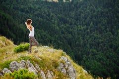 女子瑜伽放松在引人入胜的风景的地球结束时 免版税图库摄影