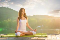 女子瑜伽-放松本质上在湖的 免版税库存照片