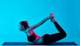 女子瑜伽exercices dhanurasana弓姿势 库存照片