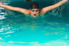 女子运动员游泳在水池的蝶泳 免版税库存图片