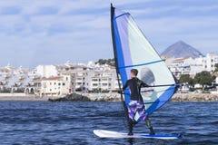 女子风帆冲浪者实践的海浪 库存图片