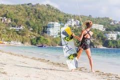 女子风筝冲浪者准备好在蓝色s的风筝冲浪的乘驾 免版税库存照片