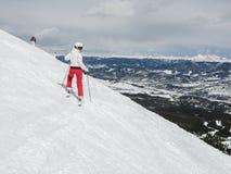 女子滑雪者准备好在小山下的奔跑 免版税库存照片
