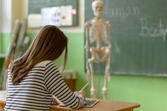 女学生使用数字式片剂的文字笔记在生物课 一代Z教育 免版税库存图片