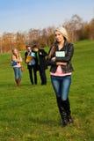 女学生和她的背景的朋友 库存图片