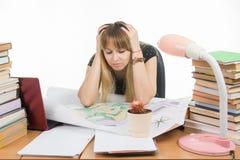 女学生在与堆的一张桌上书、图画和项目在他的手上坐拿着他的头 免版税库存照片