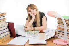 女学生在与堆的一张桌上书、图画和项目坐在手边哀伤倾斜的和眼睛关闭了 免版税库存图片