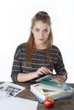 女学生坐与书的木桌,举行Ipad 微笑的女孩用苹果,书,在木桌上的ipad 库存照片