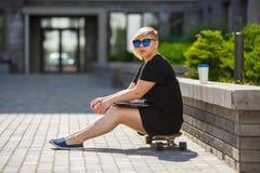 女学生坐滑板 免版税库存图片