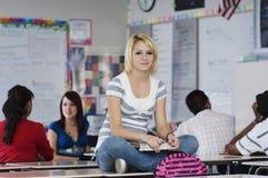 女学生坐长凳在教室 库存图片