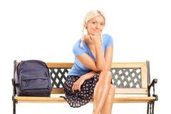 女学生坐长凳 免版税库存照片