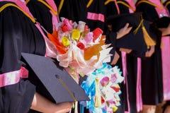 女学生毕业生举行的花花束和毕业生帽子在她的手和感到很感到骄傲和幸福上在开业日 库存图片