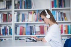 女学生研究在图书馆里,使用片剂和搜寻为 免版税库存照片
