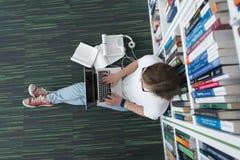 女学生研究在图书馆里,使用片剂和搜寻为 免版税库存图片