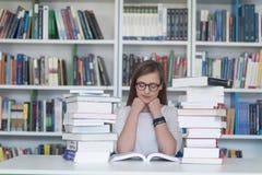 女学生研究在图书馆里,使用片剂和搜寻为 库存图片