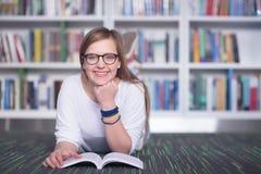 女学生研究在图书馆里,使用片剂和搜寻为 图库摄影