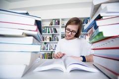 女学生研究在图书馆里,使用片剂和搜寻为 库存照片