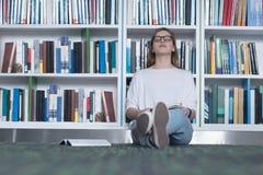 女学生研究在图书馆里 免版税图库摄影