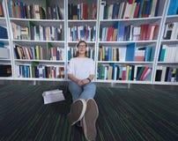 女学生研究在图书馆里 免版税库存图片
