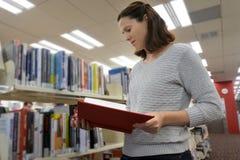 女学生研究手册在图书馆里 免版税库存图片