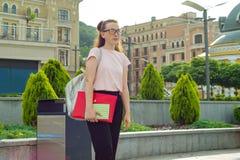 女学生16, 17岁Outdor画象  玻璃的女孩,与背包,课本 背景城市晚上街道 库存照片