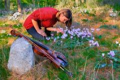 女孩、小提琴和森林花 库存照片