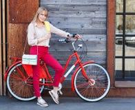 女孩、样式、休闲和生活方式-有提包的愉快的年轻行家妇女和红色葡萄酒骑自行车吃在城市街道上的冰淇凌 免版税库存照片