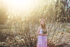 女孩、花卉花圈和春天森林 库存照片
