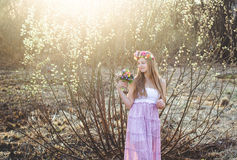 女孩、花卉花圈和春天森林 免版税库存图片