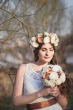 女孩、花卉花圈和春天森林 库存图片