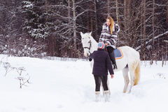 女孩、驯马师和白马在一个冬天 图库摄影