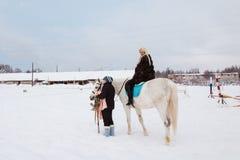 女孩、驯马师和白马在一个冬天 免版税库存图片