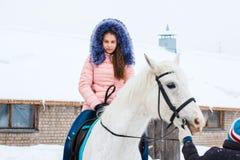 女孩、驯马师和白马在一个冬天 免版税库存照片