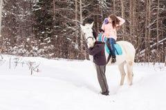 女孩、驯马师和白马在一个冬天 免版税图库摄影