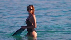 女孩一块黑游泳衣和黑玻璃的金发碧眼的女人 与身体的游泳的一个美好的模型对负 影视素材
