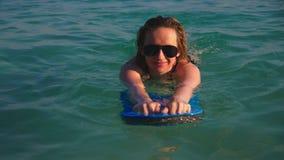 女孩一块黑游泳衣和黑玻璃的金发碧眼的女人 与身体的游泳的一个美好的模型对负 股票视频