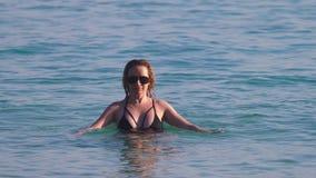 女孩一块黑游泳衣和黑玻璃的金发碧眼的女人 与身体的美好的模型获得乐趣在水晶 影视素材