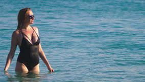 女孩一块黑游泳衣和黑玻璃的金发碧眼的女人 与身体的美好的模型获得乐趣在水晶 股票视频