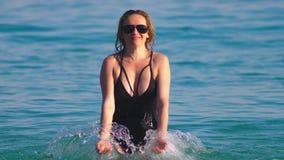 女孩一块黑游泳衣和黑玻璃的金发碧眼的女人 与身体的美好的模型获得乐趣在水晶 股票录像