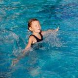 女孩一点使用的池游泳 库存照片