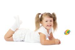 女孩一点棒棒糖微笑 图库摄影