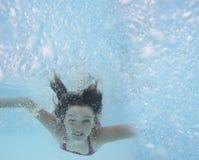 女孩一点池游泳 免版税库存照片