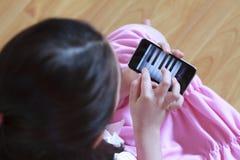 女孩一点电话钢琴使用 免版税库存图片