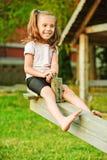 女孩一点跷跷板微笑 免版税图库摄影