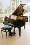 女孩一点钢琴使用 库存图片