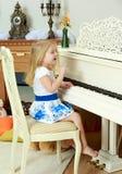 女孩一点钢琴使用 免版税库存照片