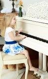 女孩一点钢琴使用 库存照片