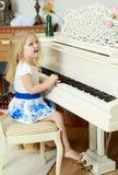 女孩一点钢琴使用 图库摄影
