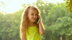 女孩一点长发谈话在背景树的智能手机美好的夏日 关闭 股票视频